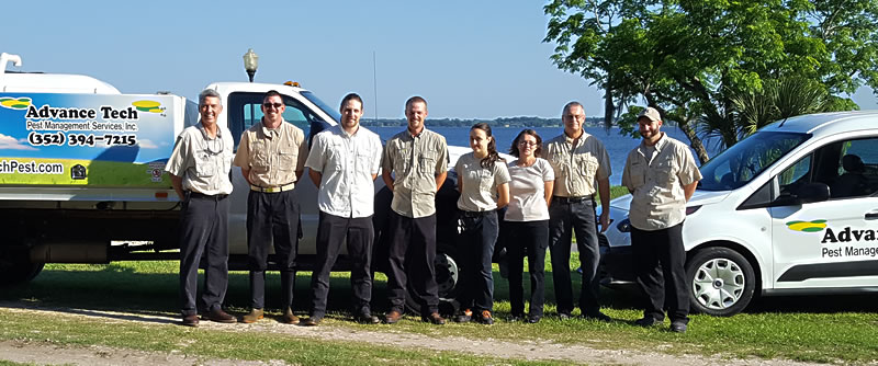 Advance Tech Pest Management crew of Clermont, Florida standing in from of their pest control and lawn care trucks.